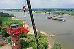 Foto: VidiPhoto<br /> <br /> BEUNINGEN – Op een respectabele hoogte van 50 meter werkt personeel van restauratiebedrijf Harm Meijer uit het Groningse Ten Boer donderdag aan de afdichting en herstelwerkzaamheden van de historische schoorsteen van de oude steenoven De Bunswaard in Beuningen bij Nijmegen. De klus aan het Rijksmonument duurt een dag, maar is nodig om schade door regenwater en vorst komende winter te voorkomen. De betonplaat die bij de eerste restauratie in 2005 was aangebracht zorgde er voor dat het vocht zich bovenaan de pijp ophoopte, waardoor stenen in de winter bevroren en knapten. De betonnen deksel is donderdag vervangen door een half open stalen kap tegen de regen, terwijl vocht wel weg kan. De kapotte stenen zijn vervangen door nieuwe. In de oude steenfabriek bevinden zich negentien woningen. Opdrachtgever voor de klus is Stichting Boei, de nationale maatschappij tot Behoud, Ontwikkeling en Exploitatie van Industrieel erfgoed.
