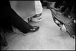 Two sets of shoes, one of a security officer who regularly comes to the shop and the other belonging to a homeless man in for a shave and a haircut. The neighborhood alleys are home to many men who spend a bit of time each day in the shop watching TV or just getting warm..