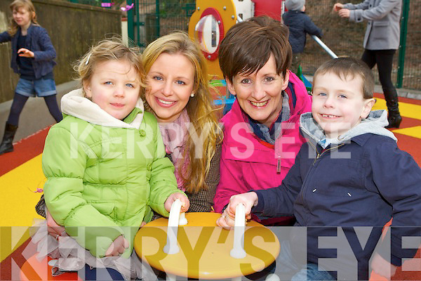 Ruby Mae Breen, Catherine Kelly, Mary C Kelly and Michael O'Connor trying out the tricycle roundabout at the official opening of Rainbows playground in Glenbeigh on Sunday.