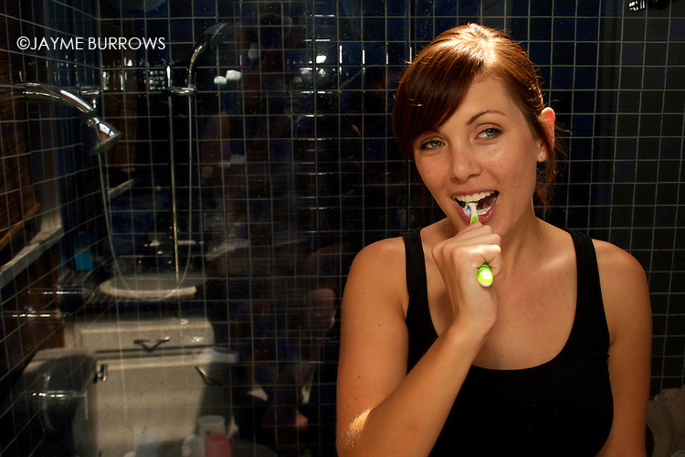 An attractive young lady brushing her teeth