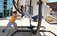 NWA Democrat-Gazette/DAVID GOTTSCHALK  Cruze Kirk, 4, pushes his mother Katie in one of the swinging chairs Monday, September 11, 2017, on the roof top patio and garden area at  Fayetteville Public Library. The library is currently in it's design phase for expansion onto property next door.