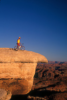 Mountain biker takes in the view from White Cracked Rock, Canyonlands National Park.