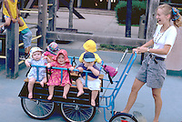 Day care worker pushing babies in large cart age 22.  St Paul Minnesota USA