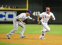 May 21, 2012; Phoenix, AZ, USA; Los Angeles Dodgers shortstop Justin Sellers (left) tags out Arizona Diamondbacks base runner Justin Upton during a sixth inning run down at Chase Field.  Mandatory Credit: Mark J. Rebilas-