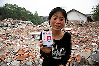 A grieving mother shows the school pass of her child, who died in a collapsed elementary school in Wufu, Sichuan, China. Over 200 students were claimed to be killed in the quake, all aged 10-13 and overwhelmingly the only child of the family, meanwhile most of the other buildings in Wufu sustained only minor damages..16 May 2008