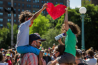 NEW YORK, NEW YORK - June 19: Two children hold up a big paper heart as they march to the front of Grand Army Plaza June 19, 2020. People gathered in New York at different locations to celebrate June 15, commemorating the day in 1865. When Union soldiers freed slaves, all movements are celebrated in the context of protests against the murder of George Floyd and other African Americans by the police in the US. (Photo by Pablo Monsalve / VIEWpress via Getty Images)