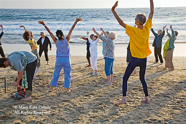 Senior men and women exercise on Playa del Rey beach, California at sunset in winter.
