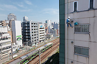 A rope access technician repairs an apartment  building  as a Yamanote Line train passes by underneath. Ebisu, Tokyo, Japan. Friday May 30th 2014