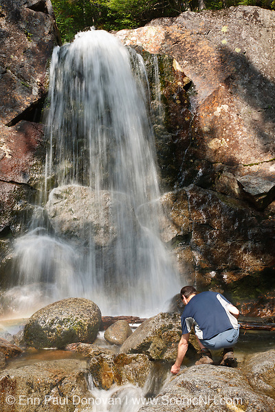 A hiker explores Thirteen Falls along Franconia Brook in the Pemigewasset Wilderness of <br />