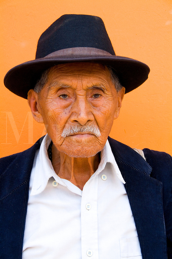 Local colorful old man with wrinkles and great eyes against bright wall with black cowboy hat in tourist village of Antigua Guatemal