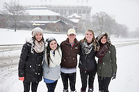 Campus Snow Day - student with Barnes and Noble and stadium in background<br />