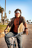 USA, Los Angeles, a man riding his bike down the Venice Boardwalk