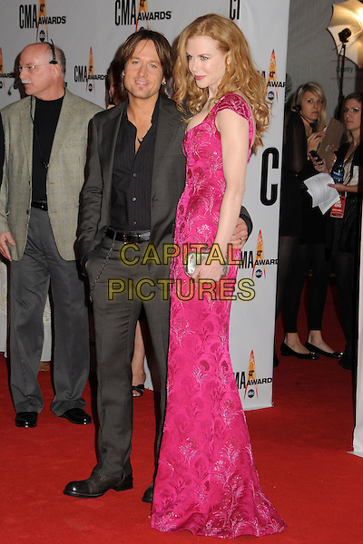 KEITH URBAN & NICOLE KIDMAN.43rd Annual CMA Awards, Country Music's Biggest Night, held at the Sommet Center, Nashville, Tennessee, USA, 11th November 2009..full length married couple husband wife long maxi pink dress grey gray suit black shirt tall short silver clutch bag cleavage arm around waist pattern embroidered patterned .CAP/ADM/LF.©Laura Farr/AdMedia/Capital Pictures.