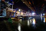 NIEUWEGEIN -  In het holst van de nacht heeft Rijkswaterstaat door Civiele Technieken deBoer – Spanlift een tijdelijke hulpbrug vanaf een ponton op de plaats van de weggeschoven Jutphasebrug (rechtsboven) over het Amsterdam-Rijnkanaal getakeld. De uit 1936 daterende boogbrug krijgt door bouwcombinatie KWS-Mercon een opknapbeurt en is een avond eerder op hoge hulppijlers verschoven waar later de stalen constructie versterkt, brugdek en pijlers gerepareerd en de brug opnieuw geverfd wordt. De Jutphasebrug zal naar een ontwerp van ingenieursbureau Movares volgend jaar 45 cm hoger worden teruggeschoven om hoger containervaart eronder mogelijk te maken. De renovatie van de Jutphasebrug is onderdeel van het project KARGO(Kunstwerken Amsterdam-Rijnkanaal Groot Onderhoud) waarbij acht stalen bruggen over het Amsterdam-Rijnkanaal, Lekkanaal en Buiten-IJ worden gerenoveerd en verhoogd. Links achter ligt de trambrug die destijds al op de juiste hoogte was gebouwd. COPYRIGHT TON BORSBOOM