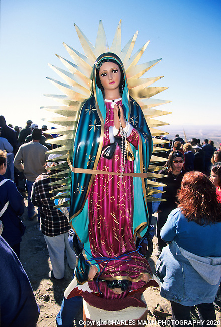 A large. colorful statue, or bulto, of the Virgin of Guadalupe ascends a mountain strapped to the back of a pilgrim during the annual Virgin of Guadalupe Feast Day celebration at the village of Tortugas, near Las Cruces, New Mexico