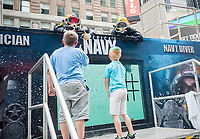 Navy Divers, Builder Second Class Estephan Lopez, left, and Construction Mechanic Second Class Ian Lemarbry, right, interact with the public in a Navy Diving Tank in Times Square in New York during Fleet Week on Saturday, May 27, 2017. The divers from the ERDGRU TWO (Explosive Ordnance Disposal Group Two) spent hours submerged in the 6800 gallon tank playing tic-tac-toe, giving high fives and otherwise enchanting the visiting public.(© Richard B. Levine)