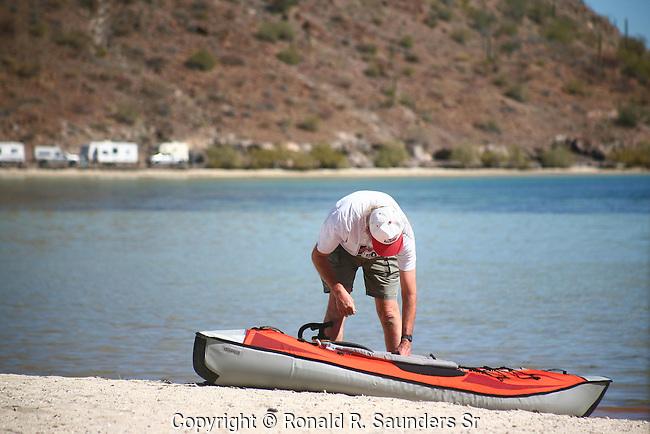 MAN INFLATES KAYAK PRIOR to ROWING on the LAKE
