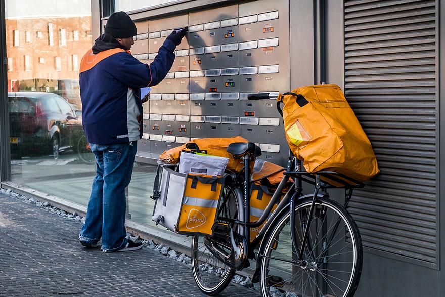 Nederland, Amsterdam, 20170214<br /> Postbezorger van Post.nl doet brieven in brievenbus bij flatgebouw. <br /> <br /> Foto: (c) Michiel Wijnbergh