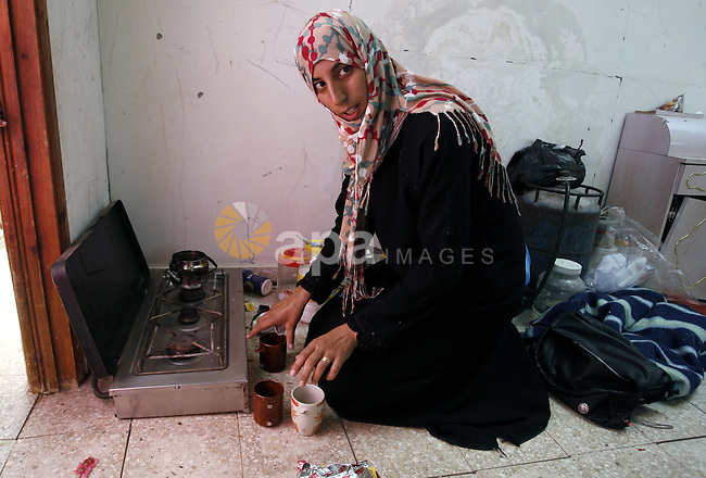 """A Palestinian woman prepares tea in a destroyed house in Khan Yunis in the southern Gaza Strip on September 11, 2014. Israel's deputy foreign minister,Tzahi Hanegbi , warned that Hamas was likely to resume """"violence"""" if it feels it has made no political gains from upcoming talks in Cairo. Photo by Abed Rahim Khatib"""