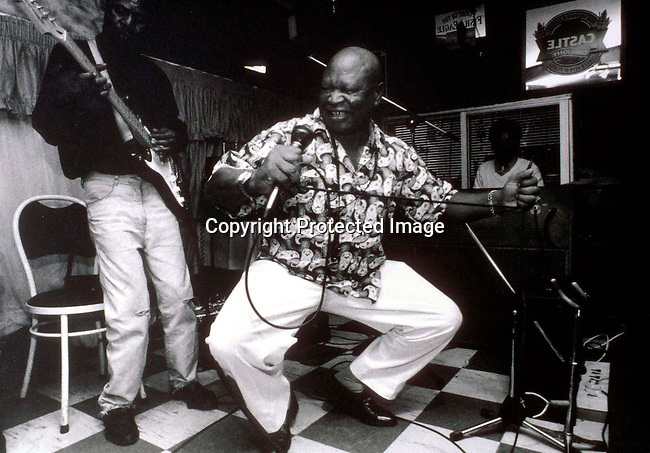 ditown00146 An unidentified band performing in a Shebeen, a (township bar) on April 24, 1997 in Soweto, South Africa. These shebeens are usually in someone's home where neighbors come to drink beer and watch sports on television. Music.Photo: Per-Anders Pettersson/ iAfrika Photos