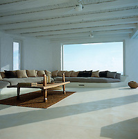 L-shaped seating and a low wooden table furnish a spacious covered roof terrace overlooking the outdoor swimming pool