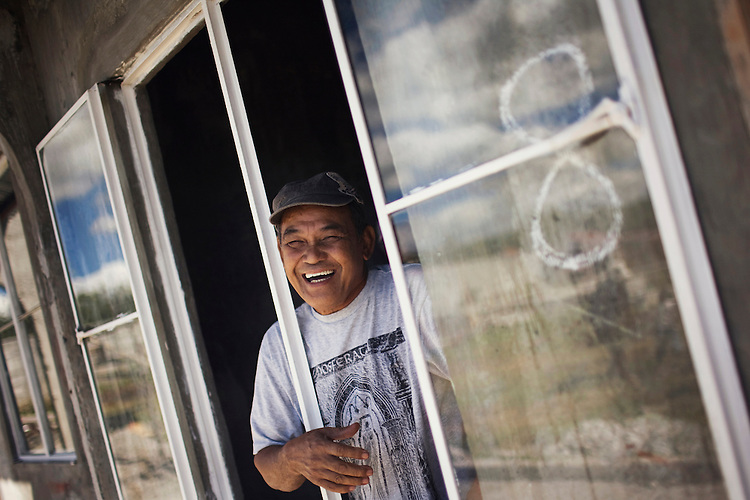A man laughs as he leans out of the window of his new home built by the Filipino non profit, Gawad Kalinga in Manila, Philippines.