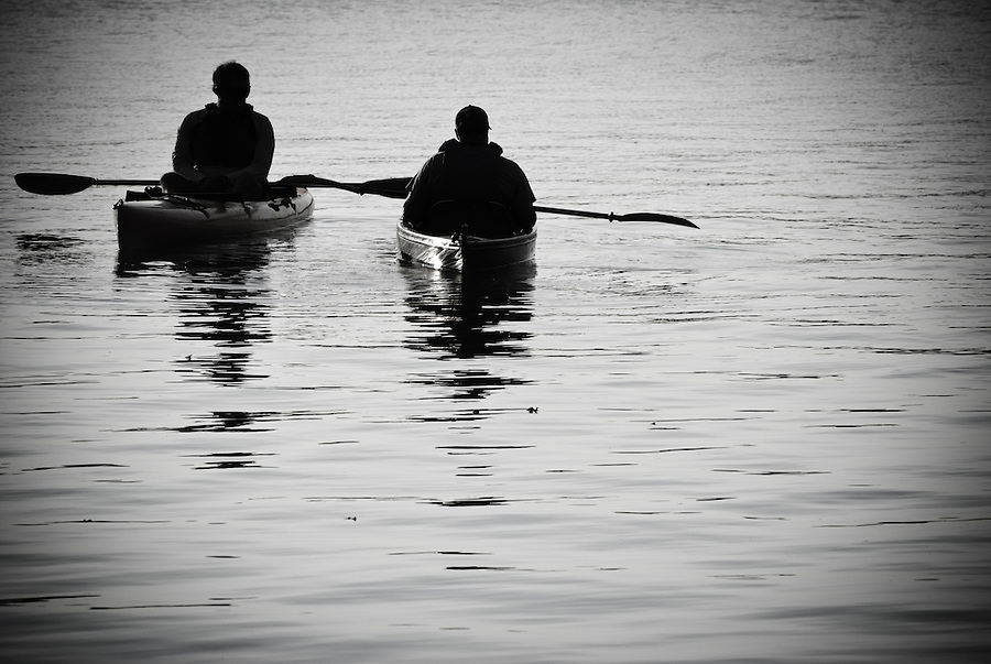 Two silhouetted kayakers floating on White Rock Lake, Dallas, Texas.