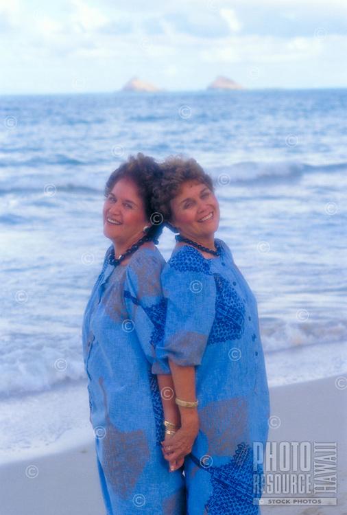 Portrait of smiling twin sisters wearing blue aloha wear at Kailua beach on windward Oahu.