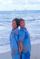 Portrait of smiling twin sisters wearing blue aloha wear at Kailua beach on windward Oahu.