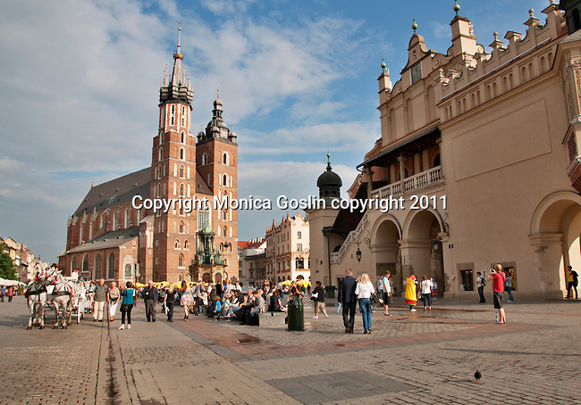 Horse carriages in front of St. Mary's Basilica in Krakow, Poland on the Main Market Square which is the largest medieval square in Europe and dates back to the 13th century