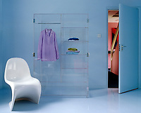 A white Verner Panton chair next to an acrylic armoire designed by Jenny Armit against a blue wall
