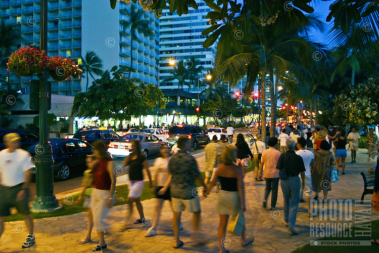 Vacationing tourist head out for the excitement of the nightlife along Kalakaua Avenue  near Waikiki Beach.