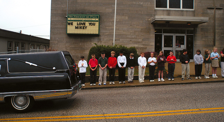 Students from St. Vincent de Paul Catholic School in Bedford line up along the street as Mike McKinney's funeral motorcade passes by en route to the cemetary. McKinney, a Ball State University student, was shot and killed by a Ball State University police officer. McKinney attended St. Vincent de Paul Catholic School as a child.