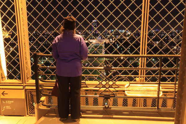 Woman viewing Montparnasse building from the Eiffel Tower at night, Paris, France. .  John offers private photo tours in Denver, Boulder and throughout Colorado, USA.  Year-round. .  John offers private photo tours in Denver, Boulder and throughout Colorado. Year-round.