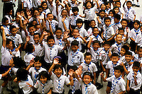Bangkok school children jumping and smiling at the camera, Thailand.