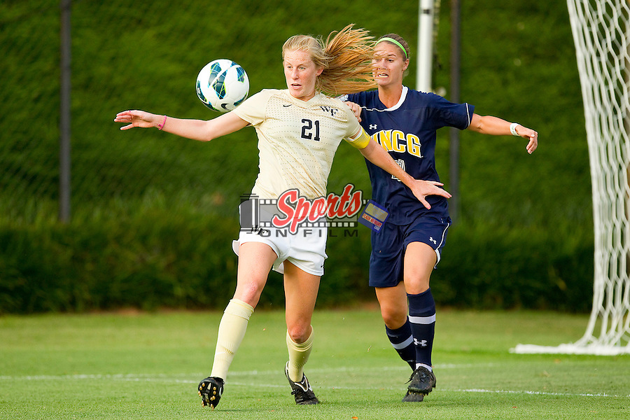 Jackie Logue (21) of the Wake Forest Demon Deacons kicks the ball away from Katie Durst (21) of the UNCG Spartans during first half action at Spry Soccer Stadium on August 24, 2012 in Winston-Salem, North Carolina.  The Spartans defeated the Demon Deacons 1-0.  (Brian Westerholt / Sports On Film)