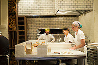 Workers prepare artisanal Montreal style bagels in the Black Seed bagelry in Nolita  in New York on Thursday, April 24, 2014.  The hand rolled  bagels are boiled in honey water and baked in a wood-burning oven. (© Frances M. Roberts)