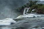 The Iguazu River flowing over the precipice of the San Martin Waterfall in Iguazu Falls National Park in Argentina.  Salto Escondido or the Hidden Waterfall is just visible as well.  A UNESCO World Heritage Site.