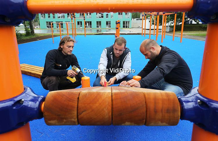 Foto: VidiPhoto<br /> <br /> ARNHEM - Op sportcentrum Papendal bij Arnhem wordt maandag de laatste hand gelegd aan een gloednieuw fitpark dat is over komen waaien uit de VS: streekworkout. Uniek is dat Nederlandse topsporters hier samen met gewone burgers kunnen werken aan hun conditie. Alle andere faciliteiten op Papendal zijn alleen bestemd voor professionele sporters. De &quot;speeltuin voor volwassenen&quot; op Papendal is een afstudeerproject van voormalig topjudoka Dennis Scherpen (m) uit Emmen en moet een voorbeeldfunctie krijgen voor de rest van Nederland. Doel is een streekworkout in alle Nederlandse gemeenten en/of wijken, om zo de fitheid van de Nederlandse bevolking te stimuleren. Streetworkout, een buitenpark met allerlei soorten rekstokken en klimtoestellen, is volgens Scherpen de snelst groeiende trend wereldwijd op dit moment. In Nederland staat het nog in de kinderschoenen. Daar wil de economiestudent nu verandering in brengen. Voor topsporters is het fitpark op Papendal een verrijking en aanvulling op het dagelijkse (kracht)training. In totaal kunnen 20-30 mensen tegelijk trainen op het nieuwe fitpark bij Arnhem. In september wordt het officieel geopend.