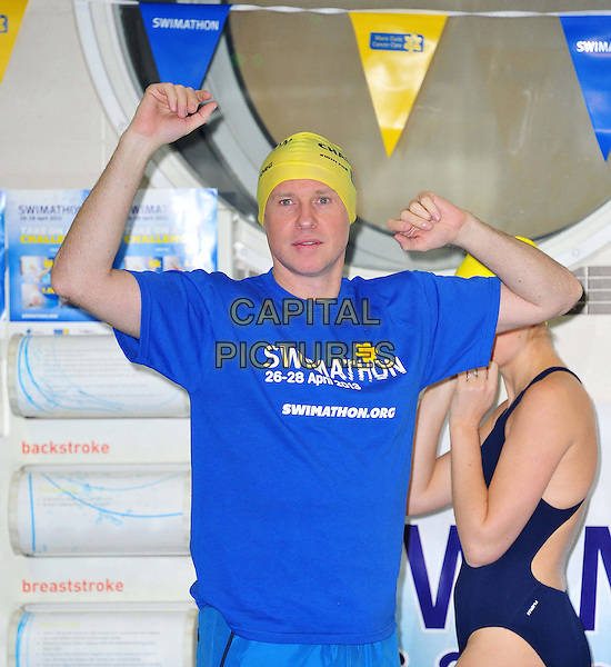 Tim Lovejoy.Swimathon 2013 launch photocall.  Launch of the annual sponsored swim in aid of Marie Curie Cancer Care and Sport Relief. Now in its 26th year, the Swimathon takes place at 645 pools nationwide.  Oasis Sports Centre, London, England..January 16th, 2013.half length blue t-shirt arms in air cap yellow.CAP/BF.©Bob Fidgeon/Capital Pictures.