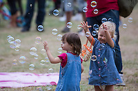 Children burst soap bubbles during a soap bubble day in a public park in Budapest, Hungary on August 25, 2013. ATTILA VOLGYI