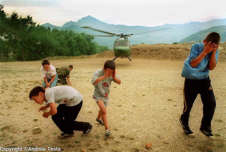 MACEDONIA. Sipkovica. 21 August 2001..Albanian children run for cover as a British Helicopter lands in Sipkovica, Headquarters of the rebel National Liberation Army in the mountains above the Albanian dominated city of Tetovo..©Andrew Testa