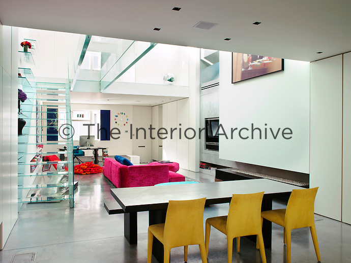 A view from the kitchen into the open plan living area under the atrium. A glass staircase and bridge access the upper mezzanines
