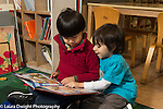 Education Preschool 4 year olds two boys looking at book together talking one pointing at picture