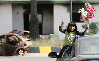 19.04.11 A little girl waves flowers and flashes the 'V' sign as she is driven through the ruins of Colonel Gaddafi's barracks, in the heart of rebel owned Benghazi, Libya.