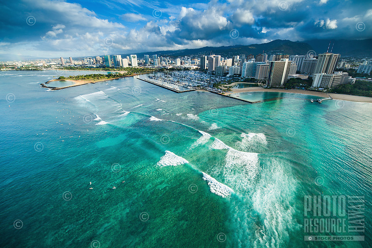 An aerial view of surfers in front of Hilton Hawaiian Village at sunrise, with Ala Moana Beach Park and Ala Wai Yacht Harbor in the distance.