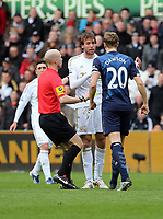 Pictured: Michael Dawson of Tottenham (R) has a go at Michu of Swansea (C) after his head clashed for a header against Scott Parker (not pictured) while match referee A Taylor (L) is trying to calm things down. Saturday 30 March 2013<br />