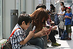 """May 9, 2010 - Tokyo, Japan - Young Japanese play Nintendo's portable video game 'DS' in front of the official Pokemon store in Tokyo on May 9, 2010. Nintendo recently announced that the DS handheld device had become the best selling gaming handheld of all time, with a total of 129 million units sold. The DS 'family' have surpassed the """"Game Boy"""" series which hit 118 million over two decades."""