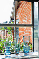 Blue glass vases are displayed on a window sill where the metal sill reflects the light.
