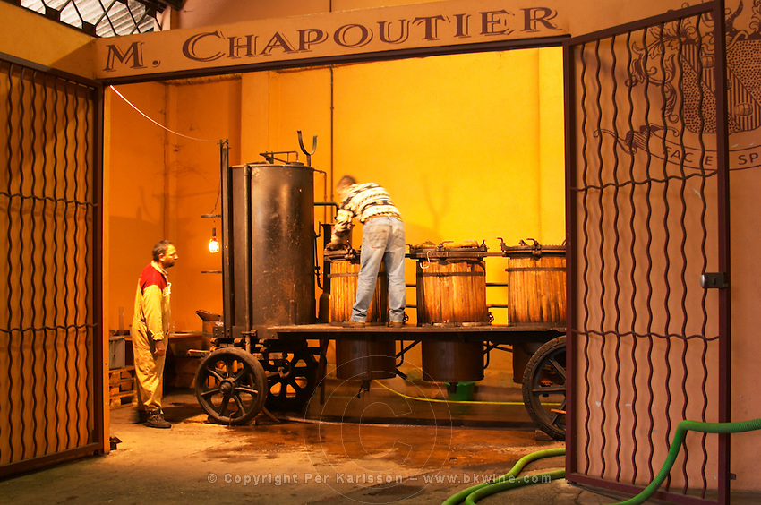 Two men working with the still. Distillation of marc and fine from wine fermentation residues at M Chapoutier using an old mobile pot still Domaine M Chapoutier, Tain l'Hermitage, Drome Drôme, France Europe